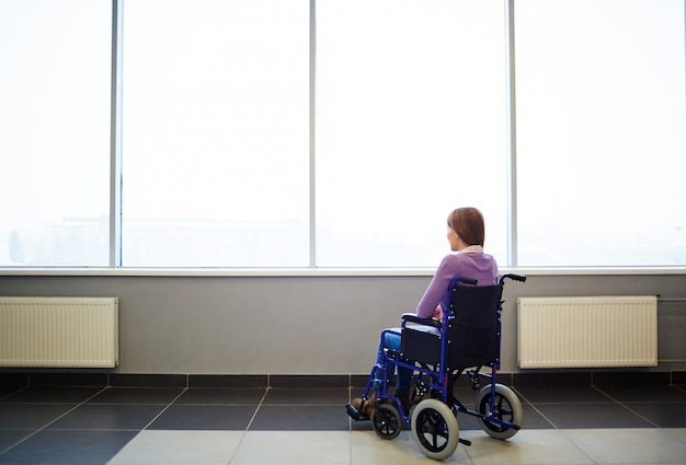 Mujer pensativa en silla de ruedas