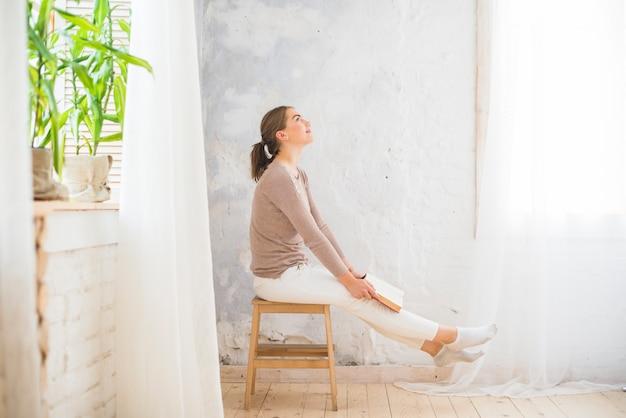 Mujer pensativa sonriente con libro sentado en el taburete en casa