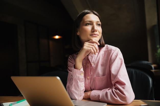 Mujer pensativa sonriente que se sienta a la mesa en la cafetería