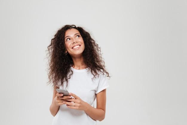 Mujer pensativa sonriente que sostiene smartphone en manos y que mira para arriba sobre fondo gris