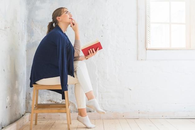 Mujer pensativa sosteniendo libro sentado en taburete
