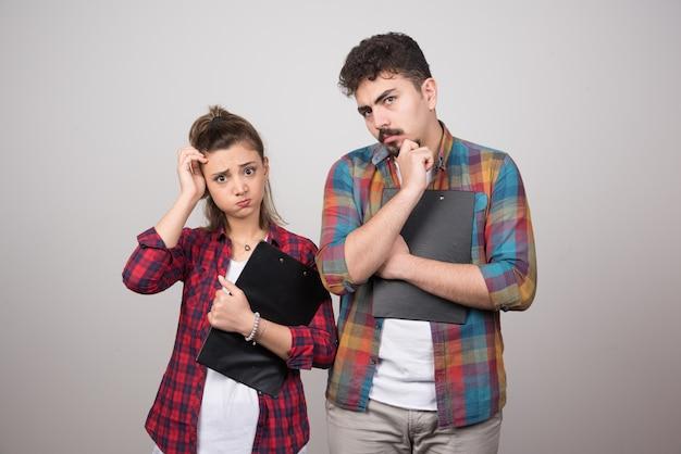 Una mujer pensativa sosteniendo un portapapeles cerca de un hombre pensativo.