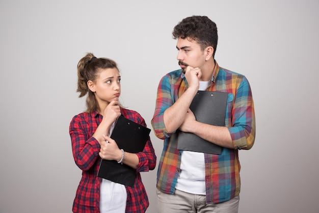 Una mujer pensativa sosteniendo un portapapeles y mirando al hombre