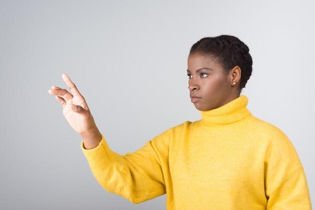 Mujer pensativa tocando la pantalla virtual con la mano