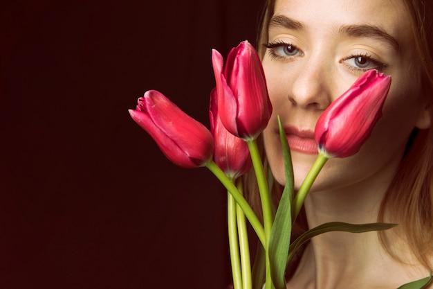 Mujer pensativa con tulipanes rojos