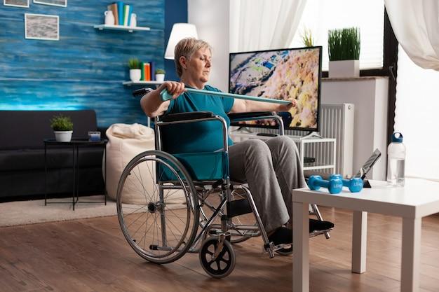 Mujer pensionista en silla de ruedas entrenamiento muscular del brazo con banda elástica de resistencia haciendo ejercicios de recuperación en la sala de estar