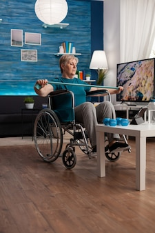 Mujer pensionista en silla de ruedas entrenamiento muscular del brazo con banda elástica de resistencia