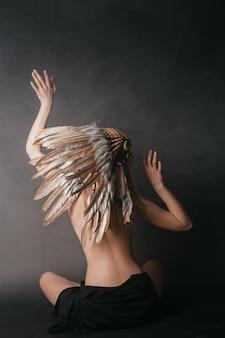 Mujer perfecta desnuda en el atuendo de indios americanos en el humo sobre un fondo gris. sombrero de plumas. misteriosa forma mística, un cuerpo sexy, una hermosa espalda.