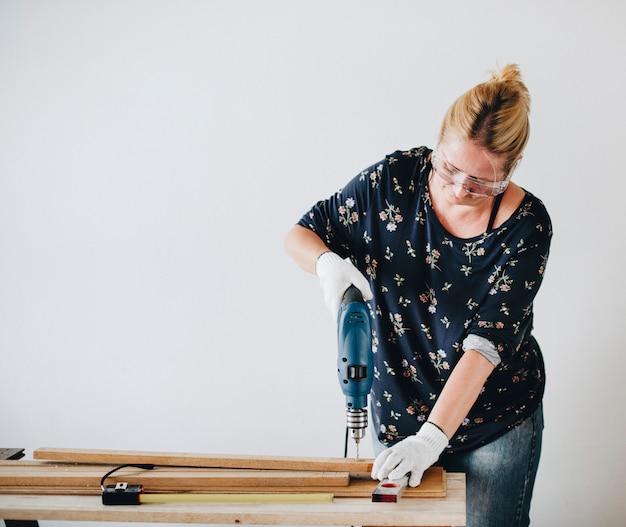 Mujer perforando en un tablón de madera