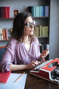Mujer periodista en anteojos escribiendo en máquina de escribir en interiores