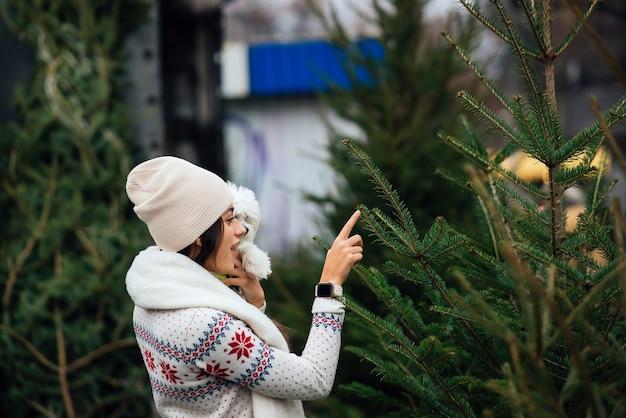 Mujer con un perro blanco en sus brazos cerca de un verde árboles de navidad en el mercado