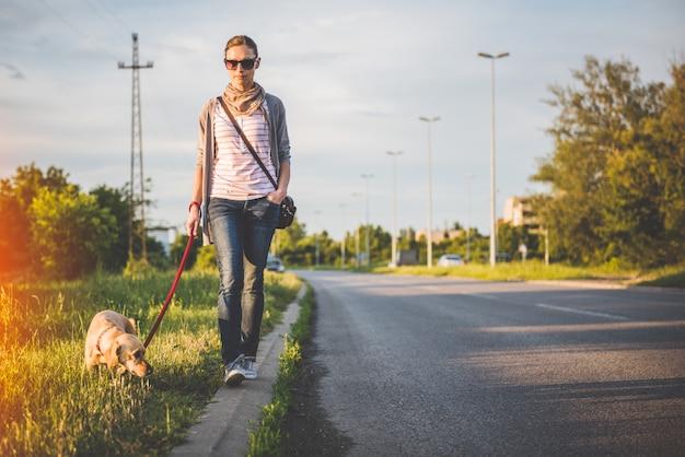 Mujer y perro caminando por la carretera