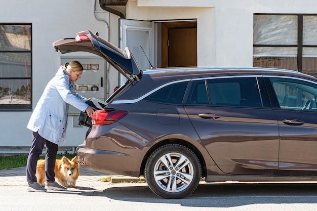 Mujer con perro cargando la maleta en el baúl del auto