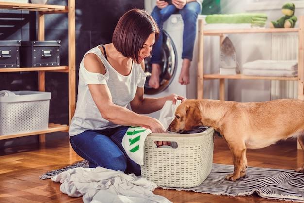 Mujer con perro clasificando ropa en el piso