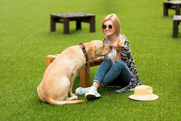Mujer y perro comiendo comida en el parque