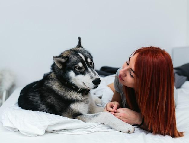 Mujer con perro grande en la cama