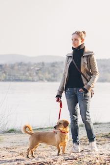 Mujer con perro ordenando junto al río