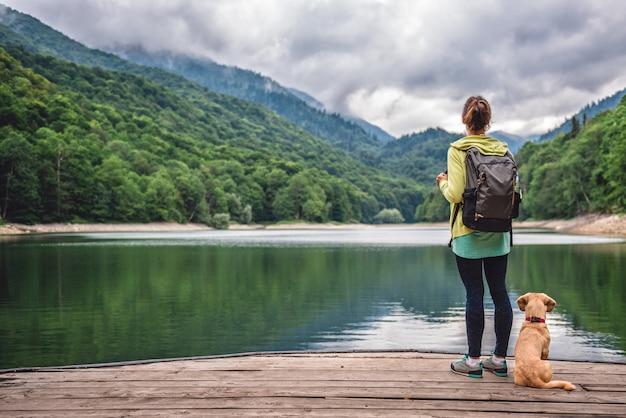 Mujer con un perro parado en el muelle junto al lago