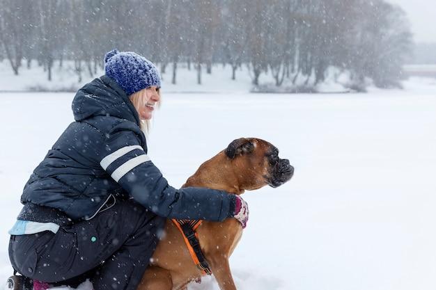 Mujer con un perro en un paseo en tiempo nevoso