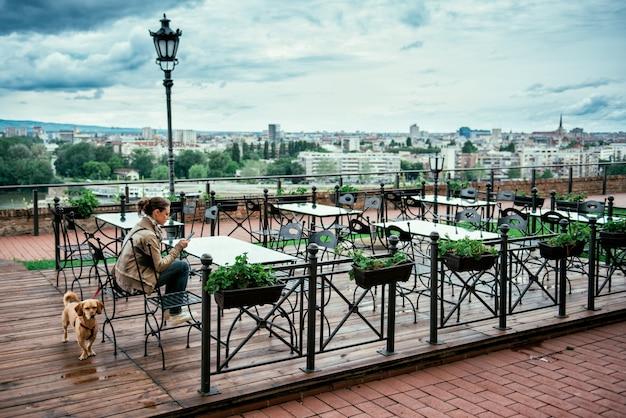 Mujer con el perro en la terraza de la cafetería vacía