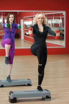 Mujer con pesas y una pierna levantada