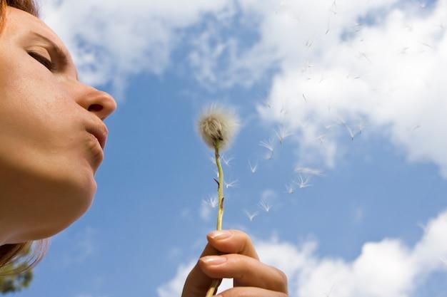 Mujer pide un deseo mientras sopla una flor