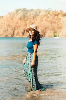 Mujer de pie en el agua por el océano
