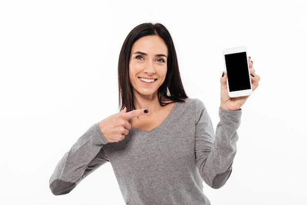 Mujer de pie aislado mostrando la pantalla del teléfono móvil.