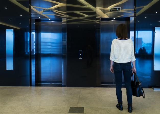 Mujer está de pie del ascensor