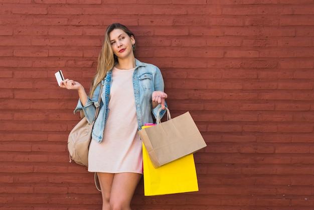 Mujer de pie con bolsas de compra y tarjeta de crédito en la pared de ladrillo
