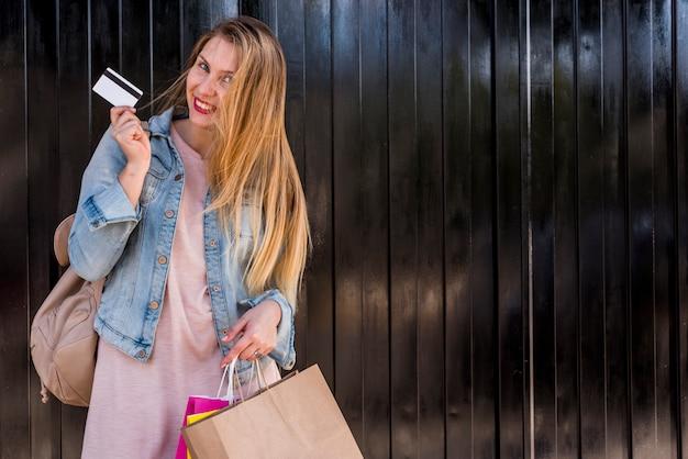 Mujer de pie con bolsas de compra y tarjeta de crédito en la pared