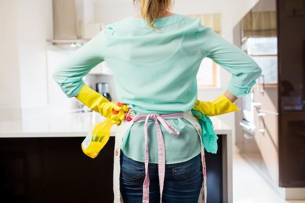 Mujer de pie con la botella del aerosol y servilleta en la cocina