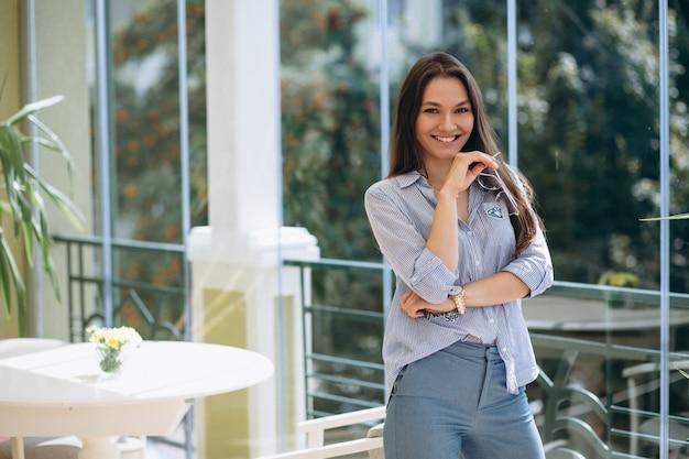 Mujer de pie en un café junto a la ventana