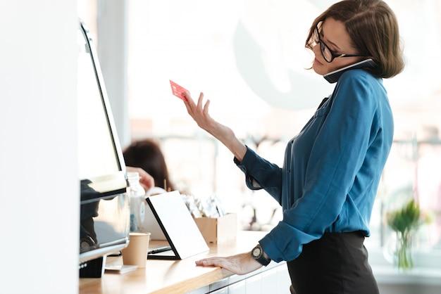 Mujer de pie en la cafetería con tarjeta de crédito hablando por teléfono