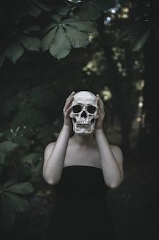 Mujer de pie con calavera en el matorral durante el día