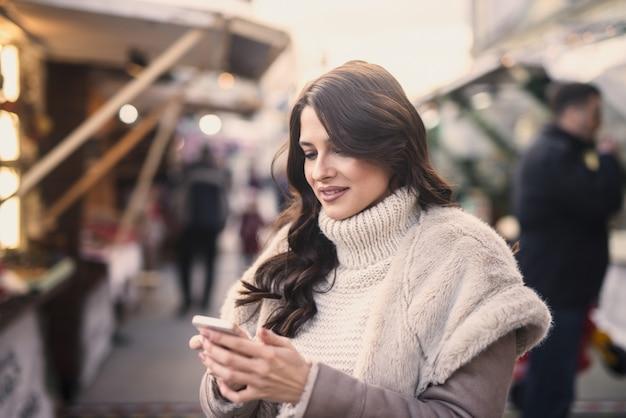 Mujer de pie en la calle y usando un teléfono inteligente para enviar mensajes de texto.