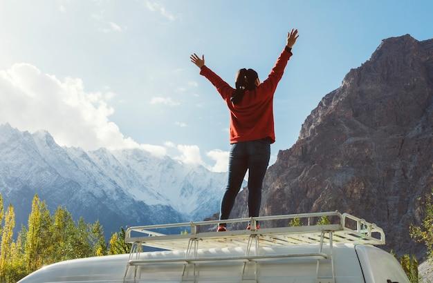 Mujer de pie en una camioneta frente a la hermosa montaña