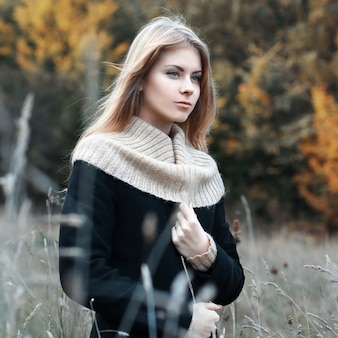Mujer de pie en un campo en otoño