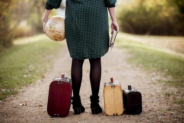 Mujer de pie en una carretera vacía cerca de su maleta mientras sostiene la biblia y un globo terráqueo