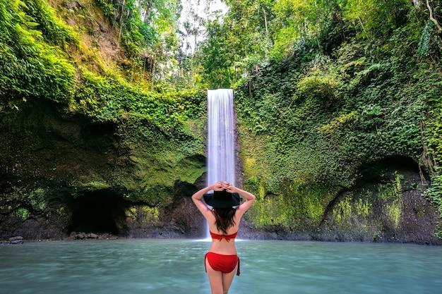 Mujer de pie en la cascada tibumana en la isla de bali, indonesia