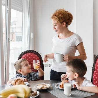 Mujer de pie cerca de sus hijos desayunando sano