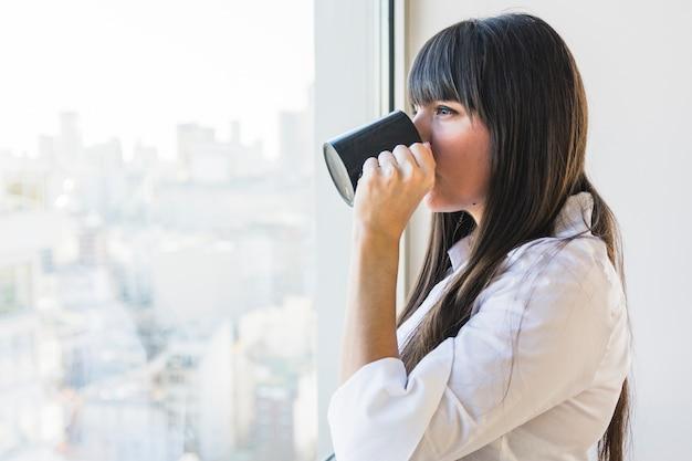 Mujer de pie cerca de la ventana tomando café
