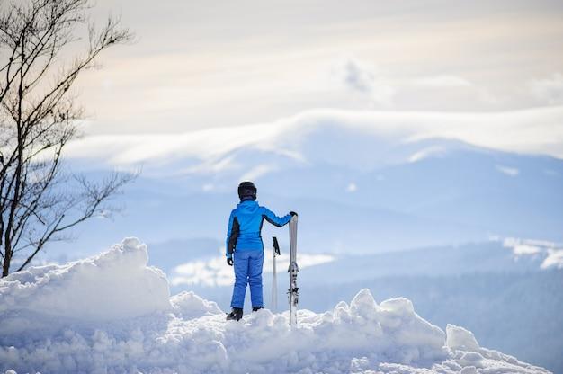 Mujer de pie en la cima de la montaña y disfrutando de la vista de las hermosas montañas de invierno