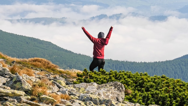 Mujer de pie en la cima de la montaña