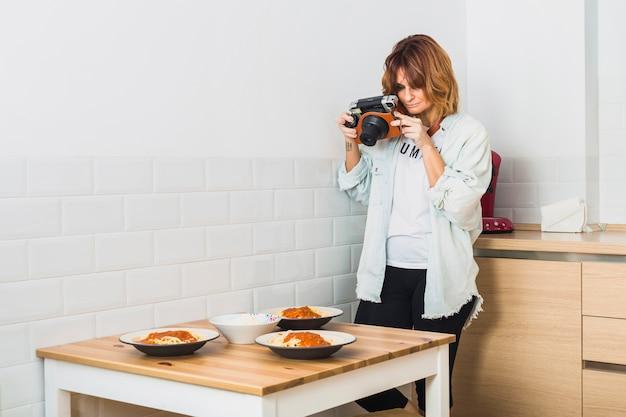 Mujer de pie en la cocina con cámara