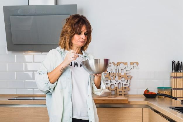 Mujer de pie en la cocina y comiendo