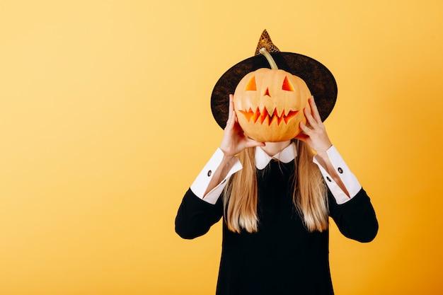 Mujer de pie contra una calabaza amarilla sosteniendo y ocultando su rostro