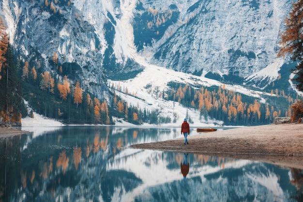Mujer de pie en la costa del lago braies en la mañana en otoño