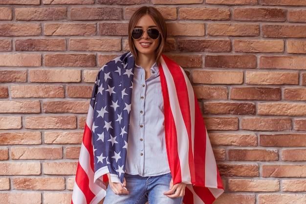 La mujer está de pie cubierta con la bandera americana.