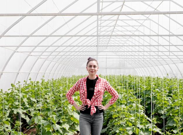 Mujer de pie delante de un invernadero